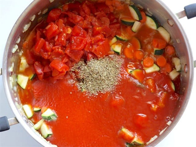 Diced Tomatoes and Tomato Sauce added to soup pot
