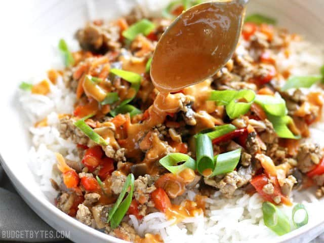 Spicy peanut sauce being drizzled over a hoisin stir fry bowl
