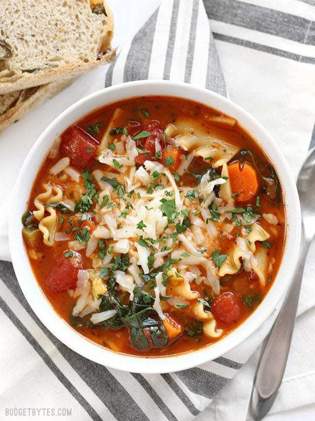 Overhead view of a bowl full of Garden Vegetable Lasagna Soup with crusty bread on the side