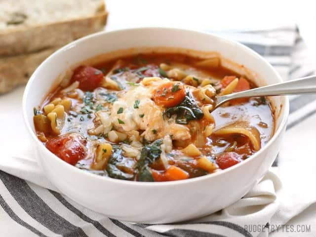 Front view of a bowl full of Garden Vegetable Lasagna soup, a spoon lifting a cheese-filled bite