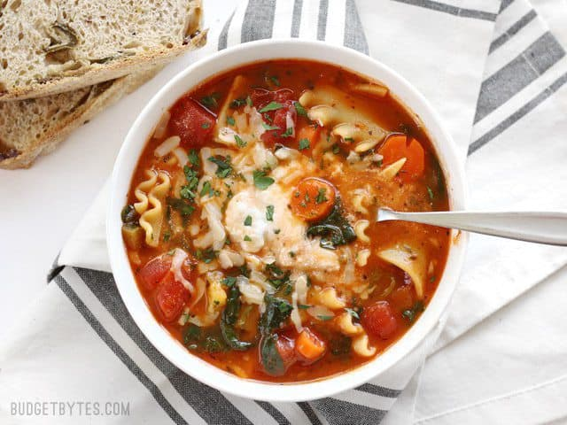 Overhead view of a bowl full of Garden Vegetable Lasagna soup with a spoon in the center, bread on the side