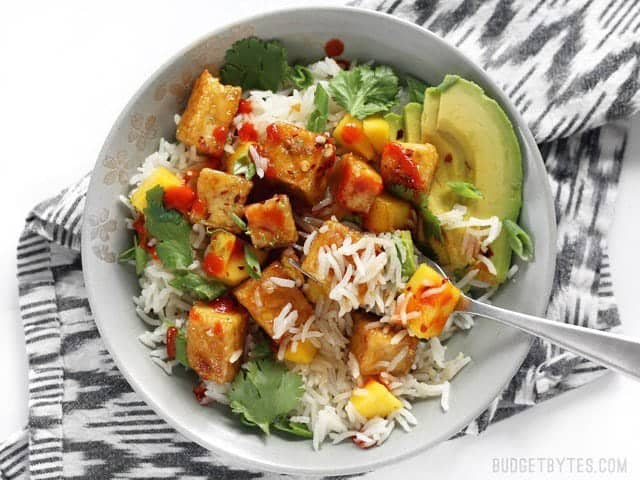 A fork digging into a Mango Coconut Tofu Bowl, with sriracha drizzled over top