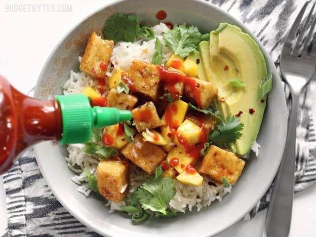 Sriracha being drizzled on a Mango Coconut Tofu Bowl