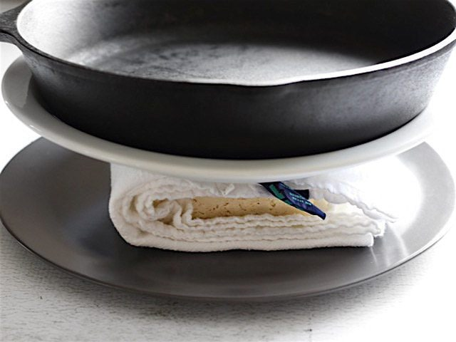 Pressing Tofu between two plates with a cast iron skillet used as the weight