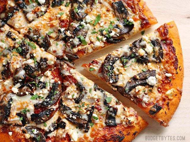 Baked and sliced Ultimate Portobello Mushroom Pizza on a wooden cutting board