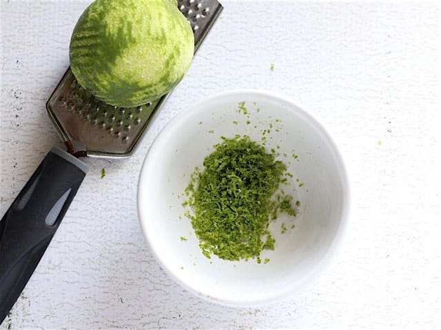 Zested Lime sitting on a microplane with a bowl of lime zest on the side