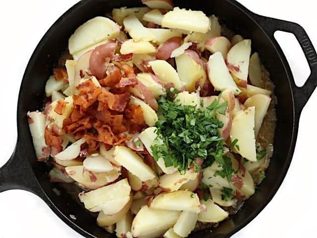 Cooked potatoes, bacon, and parsley added to dressing in the cast iron skillet