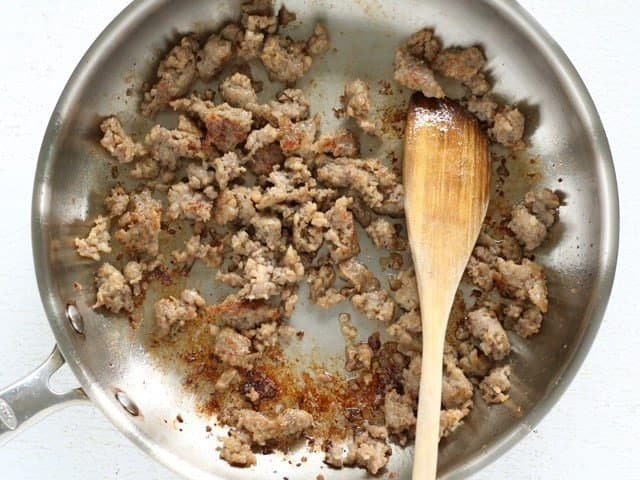 Browned Italian Sausage in the skillet with a wooden spoon