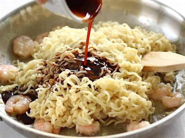 Ramen noodles added to the skillet and the dragon sauce being poured over top