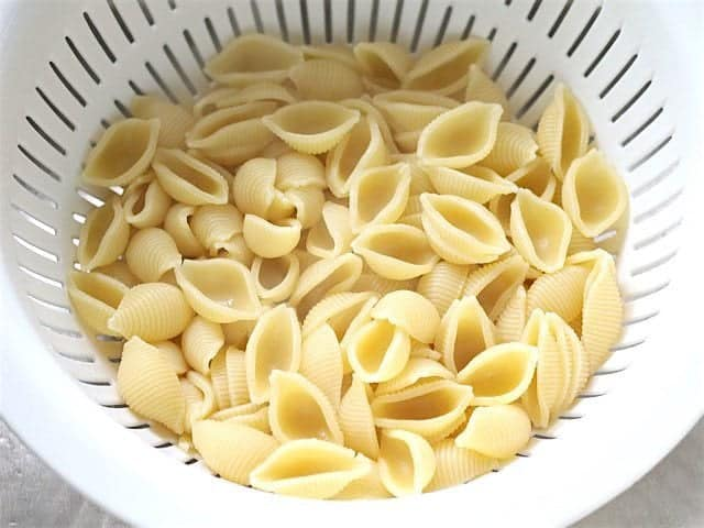 Cooked pasta draining in a white colander