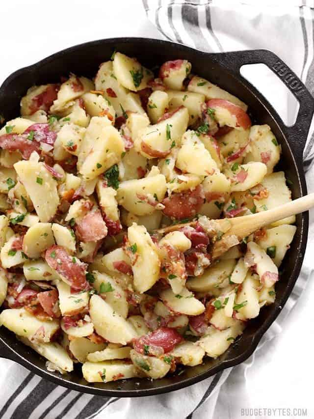 German Potato Salad in a cast iron skillet with a wooden spoon in the middle.