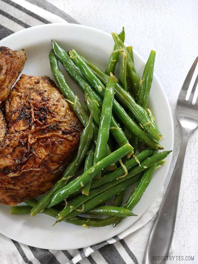 A big pile of lemon butter green beans on a plate with some roasted chicken