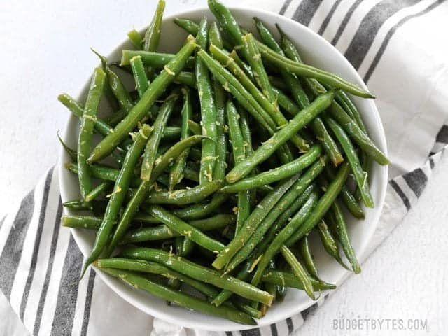 A large bowl full of Lemon Butter Green Beans garnished with lemon zest, viewed from above