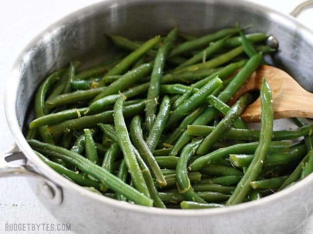 Side view of a skillet full of Lemon Butter Green Beans with a wooden spoon