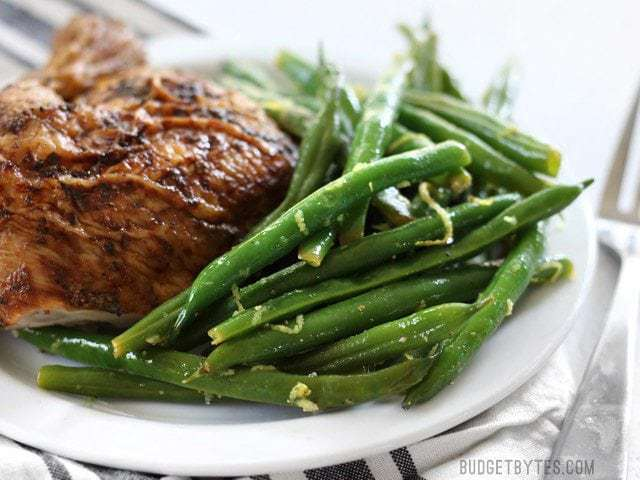Side view of a plate with Lemon Butter Green Beans and roasted chicken