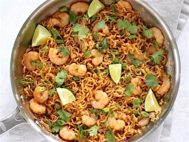 Finished Lime Shrimp Dragon Noodles in the skillet garnished with lime wedges and fresh cilantro