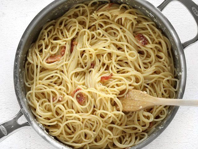 Finished skillet full of spaghetti carbonara with a wooden pasta fork