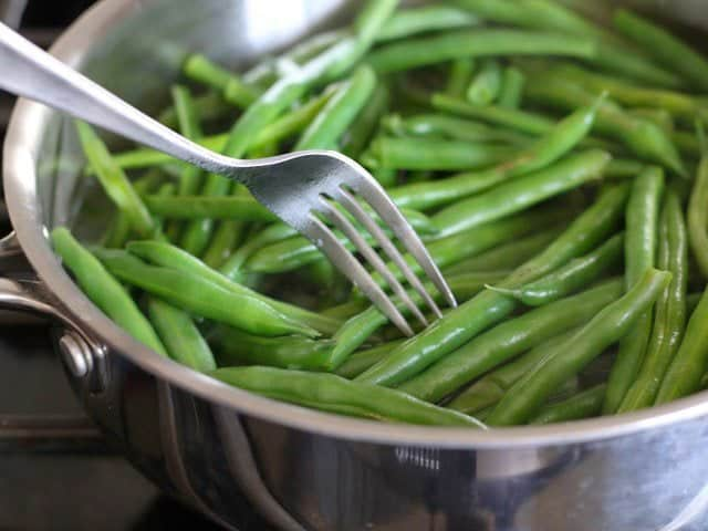 A fork testing the texture of the green beans