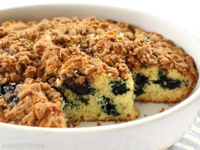 Side view of a Blueberry Buttermilk Coffee Cake with pieces cut out so you can see the crumb and juicy blueberries inside