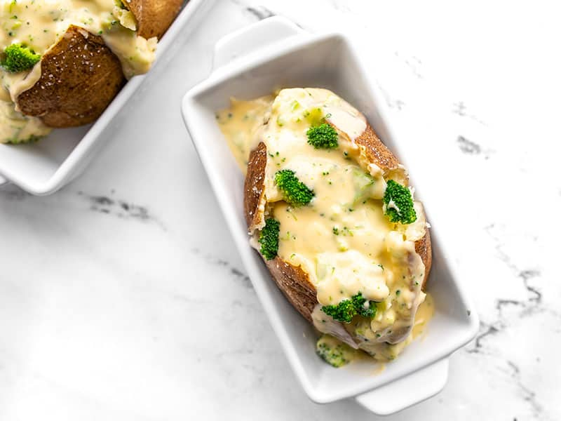 Overhead view of a broccoli cheddar stuffed potato in an individual white ceramic casserole dish