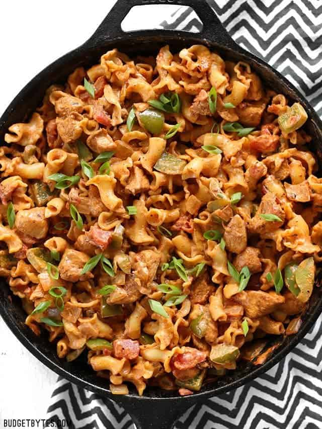 Overhead view of a cast iron skillet full of Creamy Chicken Fajita Pasta on a zig zag black napkin