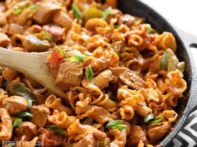 Close up of a wooden spoon scooping some Creamy Chicken Fajita Pasta out of the skillet