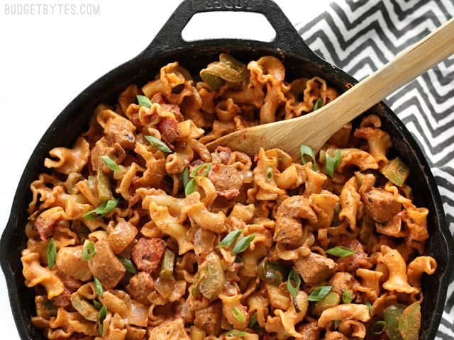 Overhead view of a skillet full of Creamy Chicken Fajita Pasta with a wooden spoon in the top