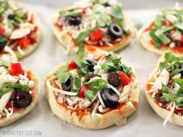 Six Freezer Mini Pizzas on a parchment lined baking sheet, ready to be frozen or baked