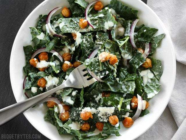 Overhead view of a Kale Salad with Cajun Spiced Chickpeas and Buttermilk Dressing in a white bowl on a black surface.