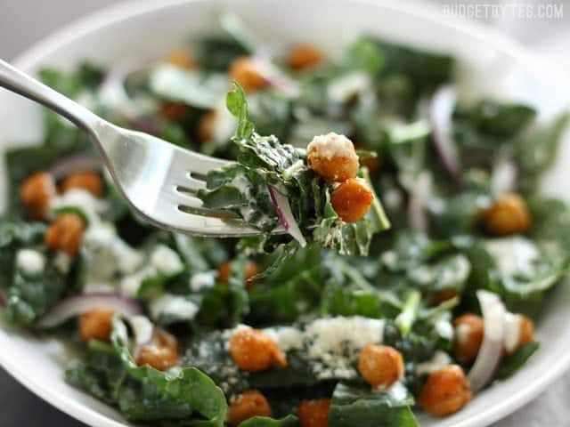 Close up of a forkful of Kale Salad with Cajun Spiced Chickpeas and Buttermilk Dressing with the bowl in the background.