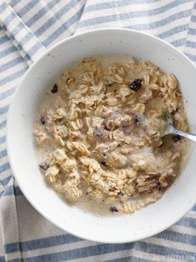 Overhead view of a bowl full of Apple Pie Overnight oats with a spoon in the middle and a striped napkin behind.