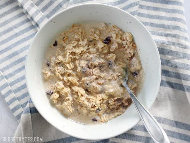 A bowl of apple pie overnight oats that has been soaked overnight and ingredients stirred together