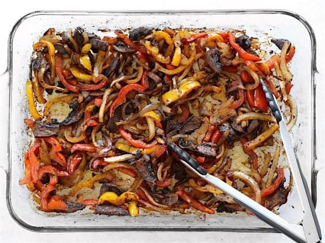 Roasted Fajita Vegetables in the casserole dish with tongs