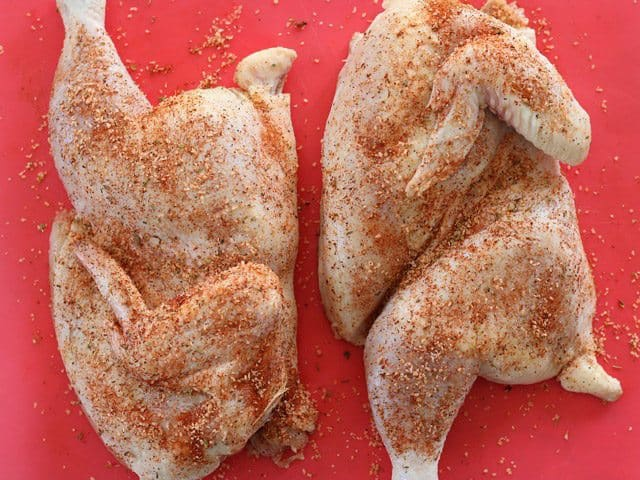 Split Chicken seasoned with spices on a red cutting board