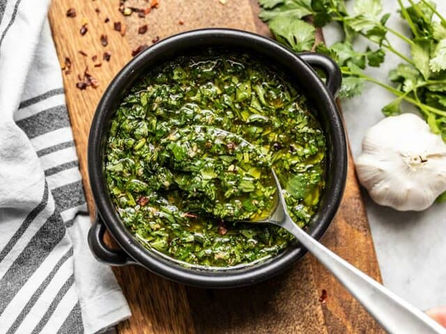 A black ceramic bowl of chimichurri with a spoon, sitting on a wooden cutting board.