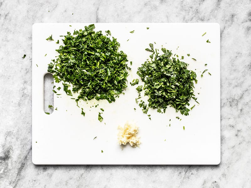 Chopped parsley and cilantro on a cutting board with minced garlic.