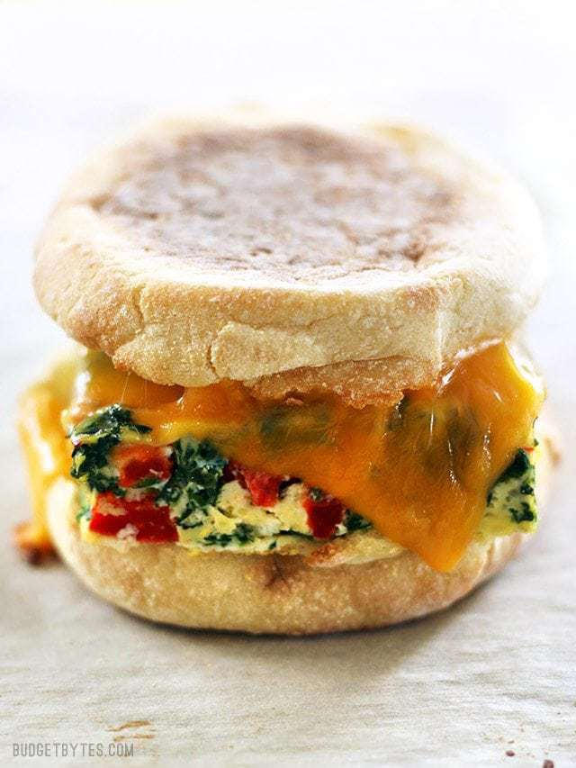 Close up side view of a Veggie Packed Freezer Breakfast Sandwich reheated with melted cheese.