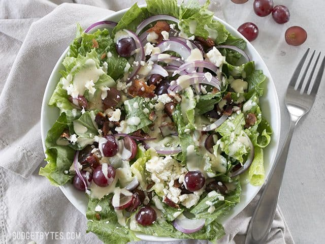 Top view of a plate of Grape Feta and Bacon Salad with a fork on the side