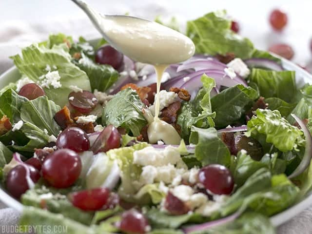 Spoonful of dressing being poured onto Grape Feta and Bacon Salad