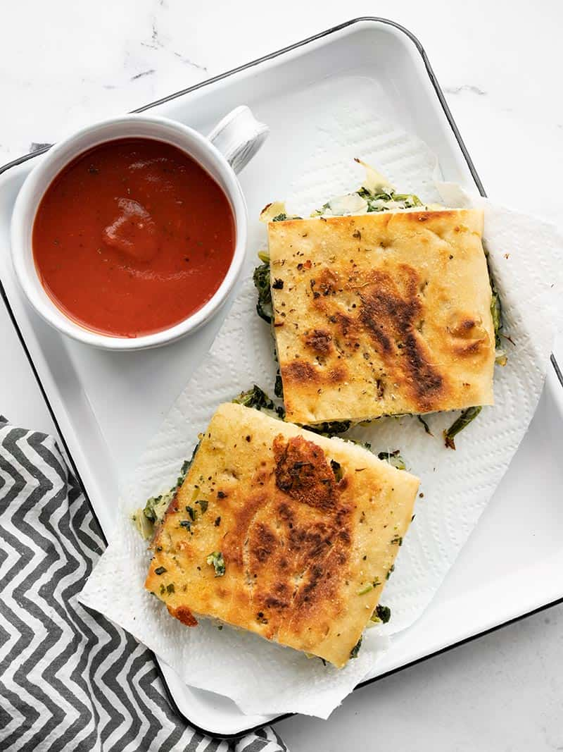 Two spinach artichoke grilled cheese sandwiches on a serving tray with a cup of tomato soup