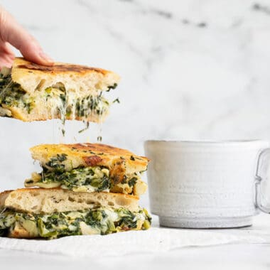 A hand picking up a piece of spinach artichoke grilled cheese with cheese stretching from the slice