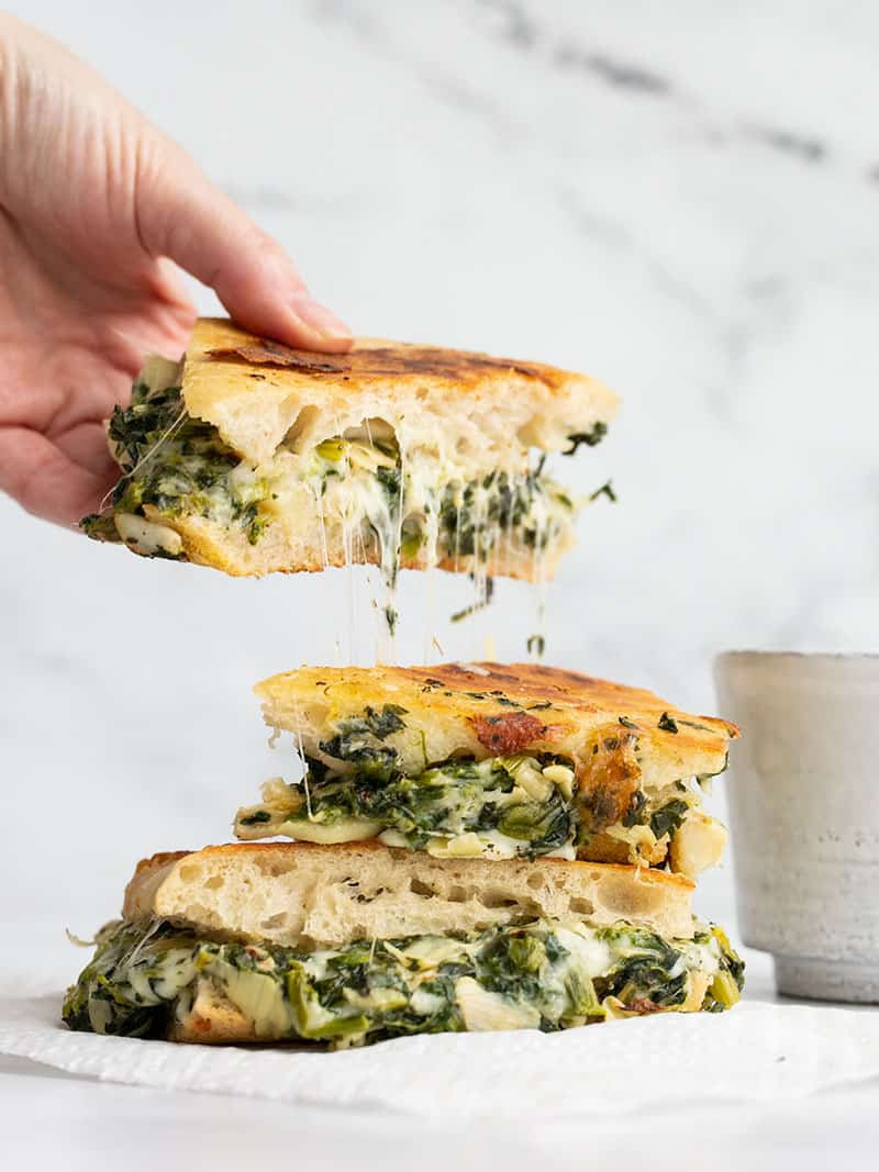 A hand picking up half of a spinach artichoke grilled cheese with cheese stretching between the pieces