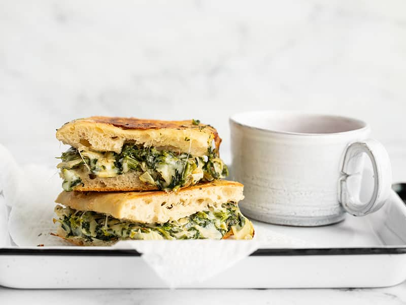 Two spinach artichoke grilled cheese sandwiches stacked on a serving tray next to a mug of tomato soup