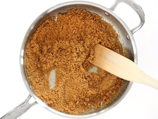 Toast Bread Crumbs in the pan with a wooden spatula