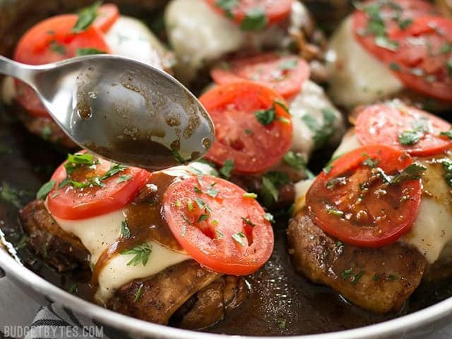 Balsamic glaze being drizzled over a piece of chicken with mozzarella and tomatoes
