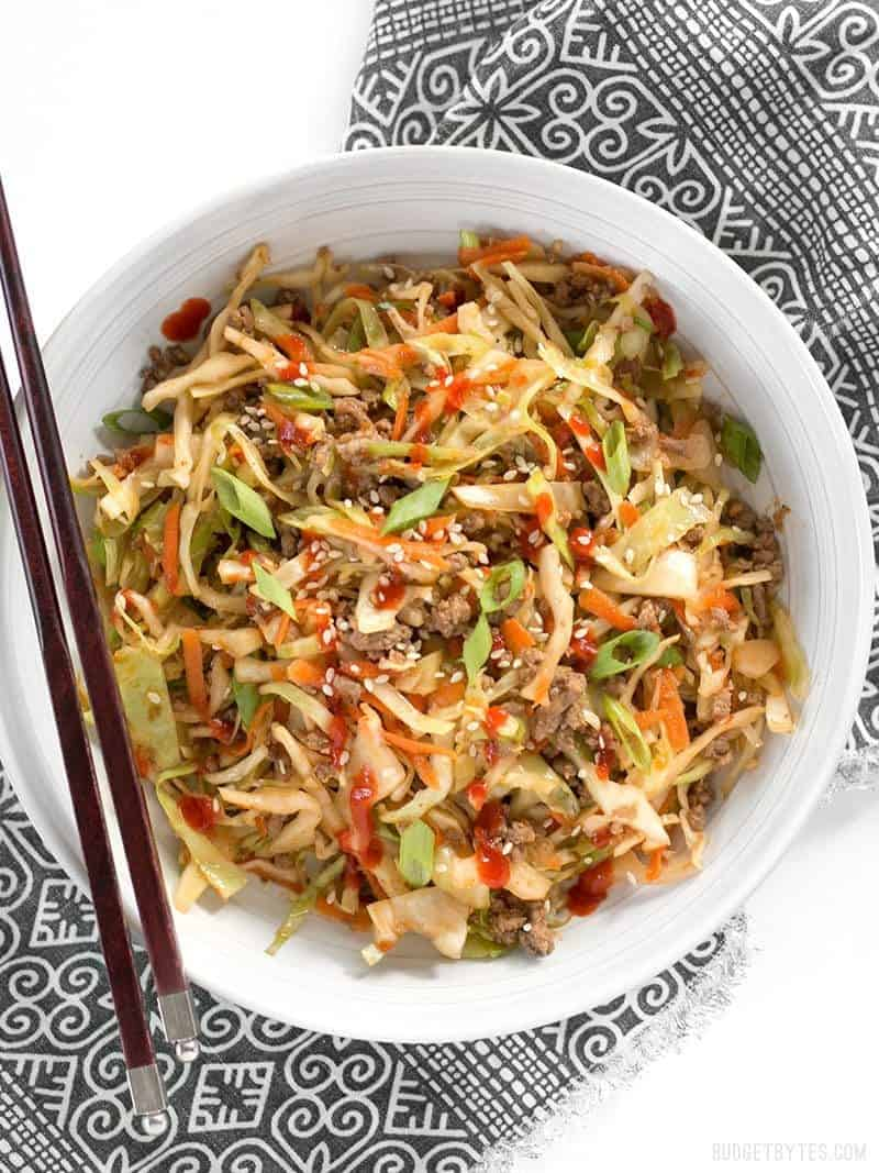 A bowl of Beef and Cabbage Stir Fry topped with sriracha, chopsticks on the side