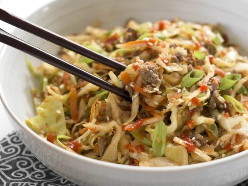 Beef and Cabbage Stir Fry in a bowl with chopsticks lifting a bite.