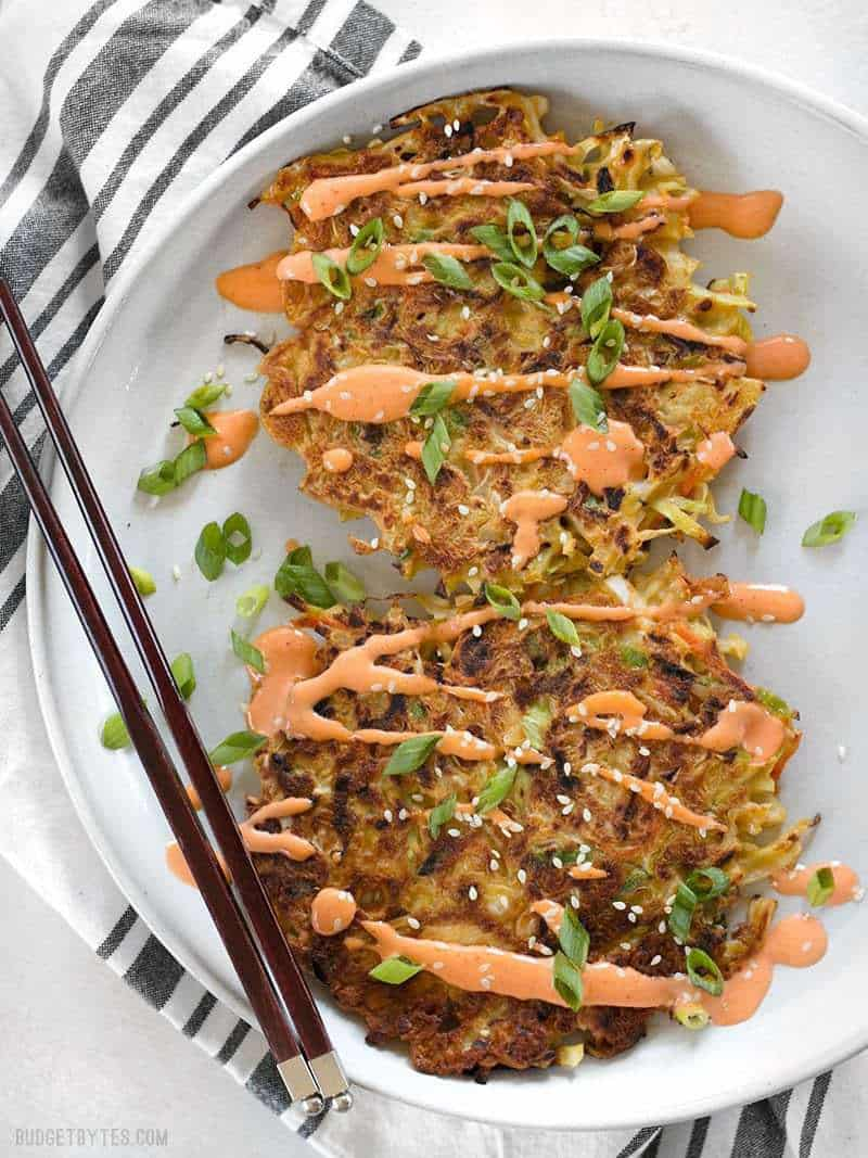 Two Savory Cabbage Pancakes on a plate drizzled with sriracha Mayo, green onion, and sesame seeds.
