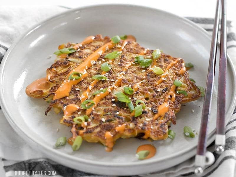 Front view of one Savory Cabbage Pancake on a plate with chopsticks, sriracha mayo, green onion, and sesame seeds