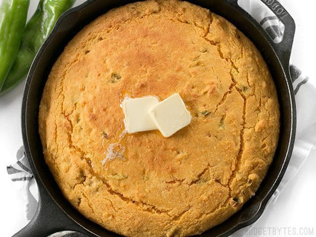 Top view of Hatch Chile Sweet Potato Cornbread in cast iron skillet, two cubes of butter on top